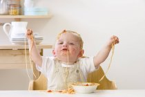 Baby sitting in high chair and eating spaghetti — Stock Photo