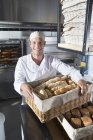 Улыбаясь Бейкер Холдинг корзины хлеба в пекарне кухня — стоковое фото