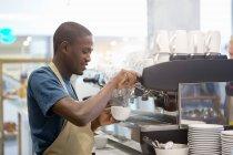 Sorridente cameriere preparazione caffè nella caffetteria — Foto stock