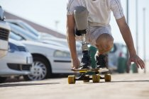 Crop image of man with artificial leg riding skateboard — Stock Photo
