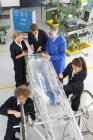 Teacher helping students constructing electric vehicle prototype in vocational school — Stock Photo