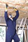 Homem em pé na escada e instalação de teto — Fotografia de Stock