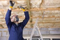 Man in coveralls  installing ceiling — Stock Photo