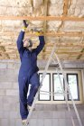 Homem no macacão instalar teto — Fotografia de Stock