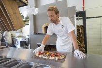 Улыбаясь шеф-повар готовит пиццу на кухне — стоковое фото