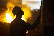 Silhouette Of Worker In Foundry With Molten Metal Being Poured — Stock Photo