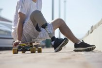 Crop of man with artificial leg sitting on skateboard at urban scene — Stock Photo