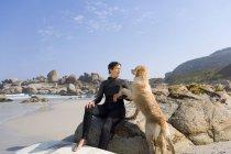 Feminina surfista sentado sobre as rochas com cachorro na praia — Fotografia de Stock