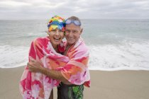 Smiling mature couple wrapped in towel on beach — Stock Photo