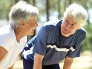 Senior couple smiling at each other at park with defocussed background — Stock Photo
