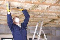 Homem da máscara protetora instalar teto — Fotografia de Stock