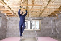 Man standing on ladder and installing ceiling — Stock Photo