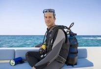 Людина, що сидить на човні підготовка ходив підводного плавання — стокове фото
