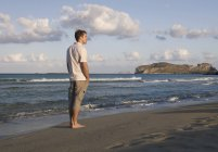 A man walking alone on a beach — Stock Photo