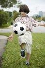 Vista frontale di giovane ragazzo calcio calci — Foto stock