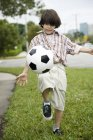 Vue de face du jeune garçon, coups de pied de football — Photo de stock