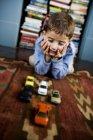 Niño jugando con coches de juguete en el piso - foto de stock