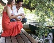 Jeune couple cygnes d'alimentation — Photo de stock