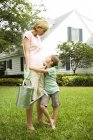 Daughter hugging mother carrying watering can — Stock Photo