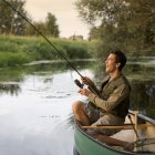 Young man fishing in boat — Stock Photo