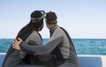 Пару сидить на човні підготовка ходив підводного плавання — стокове фото