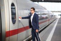 Uomo adulto business media raggiungendo per treno porta, Monaco di Baviera, Baviera, Germania, Europa — Foto stock