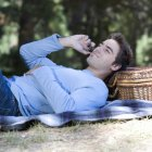 A young man using a mobile phone at a picnic — Stock Photo