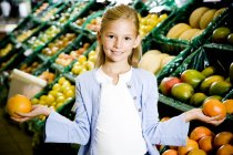 Portrait of young girl holding two grapefruits in supermarket — Stock Photo
