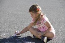 Jeune fille écrit à la craie sur le terrain de jeu — Photo de stock