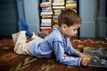 Little boy reading picture book lying on the floor — Stock Photo