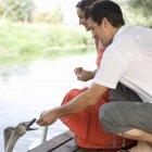 Young couple feeding swans — Stock Photo