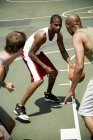 Three men playing basketball on an outdoor court — Stockfoto