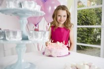 Girl in pink dress standing near birthday cake — Stock Photo