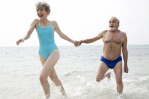 Portrait of a senior couple hand in hand running in the sea — Stock Photo