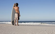 A surfer standing on a beach and looking on waves — Stock Photo