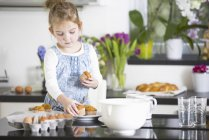 Young girl arranging cupcakes in kitchen — Stock Photo