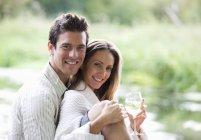 Junges paar sitzt an einem Fluss, Frau mit Weinglas — Stockfoto