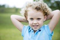 Petite fille avec les mains derrière la tête — Photo de stock