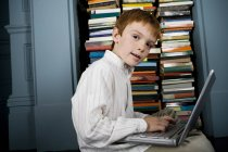 Boy with laptop looking at camera — Stock Photo