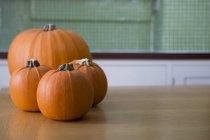 Calabazas de Halloween naranja sobre una mesa de cocina - foto de stock