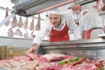 Усміхаючись м'ясника організацію м'ясо у вітрину — стокове фото