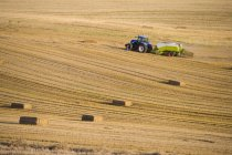 Tractor with straw baler driving in field — Stock Photo