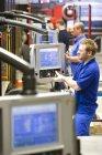 Travailleurs d'exploitation informatiques contrôlée machines dans l'usine fabrique des appareils d'éclairage en aluminium — Photo de stock