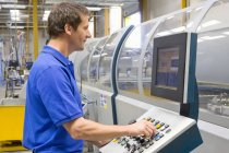 Worker adjusting buttons on factory control panel — Stock Photo