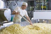 Vue latérale du fromager ratisser râpé cheddar ferme — Photo de stock