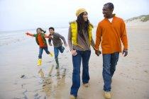 Family walking and running on beach — Stock Photo