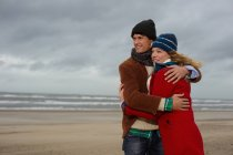 Couple standing on beach in winter and embracing — Stock Photo