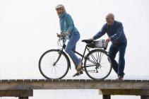 Старший пара на дерев'яні jetty, велосипед їзда жінка — стокове фото