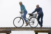 Pareja senior en bicicleta de madera el embarcadero, mujer a caballo - foto de stock