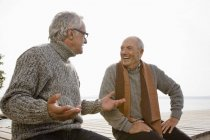 Two senior men sitting on a wooden jetty, talking to each other — Stock Photo